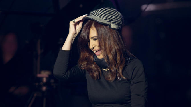 """Argentina's President Cristina Fernandez tries on a hat given to her by a supporter at a government event outside the government house in Buenos Aires, Argentina, Saturday, May 25, 2013.  Fernandez's government and supporters are celebrating 10 years since she and her late husband have held office, and the 203th anniversary of the Argentina's May Revolution. This year's election will determine whether she has the votes in congress to undo constitutional term limits and extend her rule beyond 2015. But she suggested Saturday night that she won't try. She said """"I'm not eternal, nor do I want to be."""" (AP Photo/Natacha Pisarenko)"""