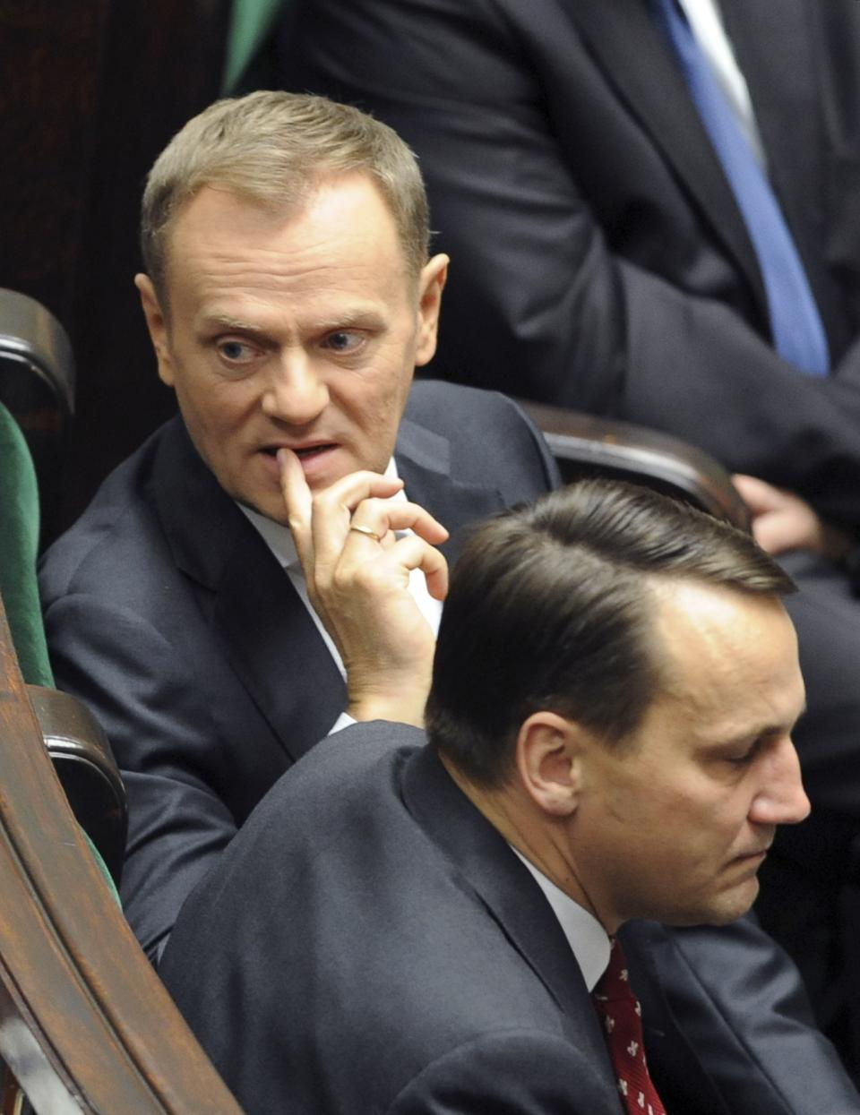 Polish Prime Minister Donald Tusk, left,  looks back as he sits next to Foreign Minister Radek Sikorski during the first session of the new Polish Parliament, in Warsaw, Poland, Tuesday, Nov. 8, 2011. (AP Photo/Alik Keplicz)