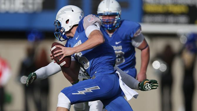 Air Force quarterback Nate Romine, front, is stopped after a short gain by Colorado State linebacker Aaron Davis in the first quarter of an NCAA college football game at Air Force Academy, Colo., on Friday, Nov. 28, 2014. (AP Photo/David Zalubowski)