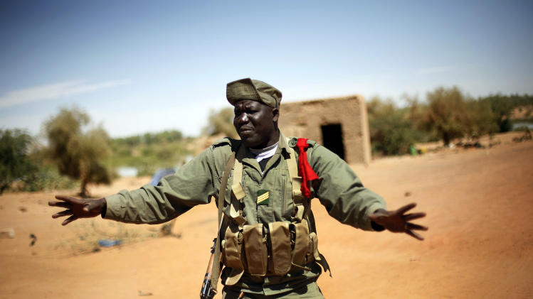A Malian soldiers  tells journalists not to film the entrance of Gao, northern Mali, Friday Feb. 8, 2013, where a suicide bomber on a motorcycle killed himself attempting to blow up an army checkpoint. It was the first known  time a suicide bomber has operated in Mali. (AP Photo/Jerome Delay)