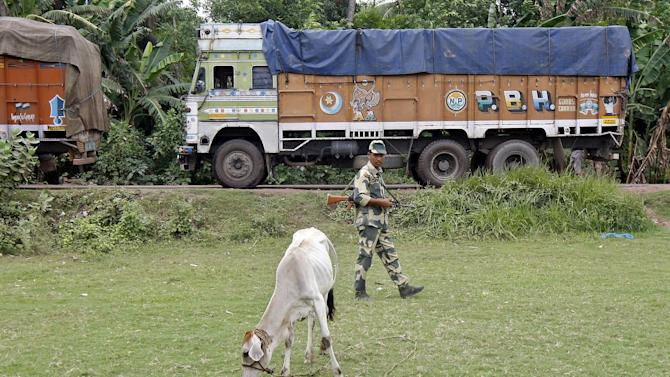 Indian BSF soldier patrols as trucks wait to cross the India-Bangladesh check-post in West Bengal