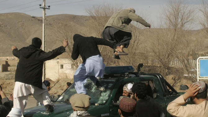 Protesters vandalize a police truck during an anti-US demonstration over burning of Qurans at a US military base in Afghanistan, in Herat, Friday, Feb. 24, 2012. (AP Photo/Hoshang Hashimi)