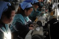 Laborers work in a clothing factory in Huaibei, central China&#39;s Anhui province, on January 10, 2013. Foreign direct investment in China declined for the first time in three years in 2012, official data shows, amid economic turmoil in developed markets and a slowdown at home