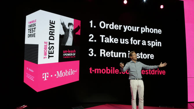 T-Mobile Chief Marketing Officer Mike Sievert talks about his company's new program that offers a free seven-day test drive of an Apple iPhone 5S at T-Mobile's Uncarrier 5.0 event, Wednesday, June 18, 2014, in Seattle. (AP Photo/Ted S. Warren)