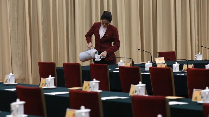 A hostess pours tea into a cup as she prepares for the Beijing delegation's group discussion during the National People's Congress (NPC) in Beijing