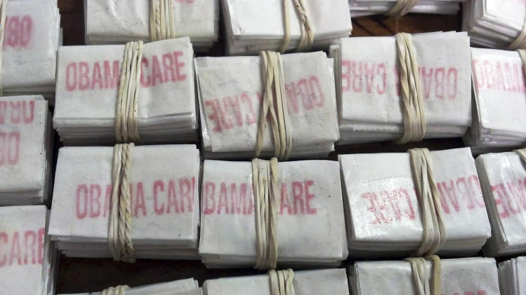 "This photo released on Friday, Dec. 20, 2013 by the Massachusetts State Police via Facebook shows some of the 1,250 packets of heroin labeled ""Obamacare"" and ""Kurt Cobain"" which state police troopers confiscated during a traffic stop in Hatfield, Mass. Four people were charged with heroin trafficking. (AP Photo/Massachusetts State Police)"
