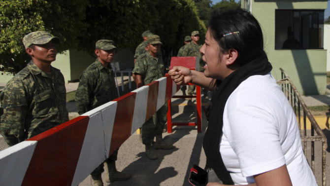 An unidentified woman shouts at Mexican army soldiers standing guard in front of the entrance to the 27th Infantry Battalion base in Iguala, Mexico, Thursday, Dec. 18, 2014. Relatives of the 43 missing students blocked the entrance to the base in protest over the army's alleged responsibility or lack of response during the night of Sept. 26 when 43 students were taken by municipal police and then handed over to a drug gang to be killed and then the bodies burned, according to the results of the Attorney General's investigation. (AP Photo/Felix Marquez)
