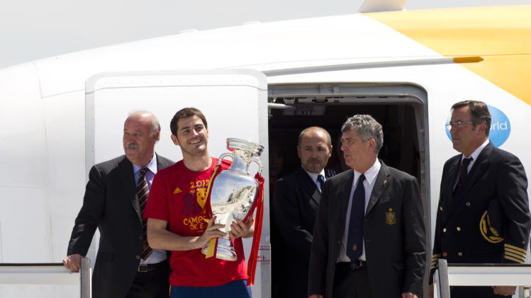 Spain's captain Iker Casillas, 2nd right, walks out of the plane holding the trophy alongside coach Vicente del Bosque, left and the president of the Spanish football association Angel Villar, 4th left, on arrival at Barajas airport in Madrid Monday July 2, 2012. Spain won the Euro 2012 soccer championship final against Italy in Kiev, Ukraine, Sunday. (AP Photo/Paul White)