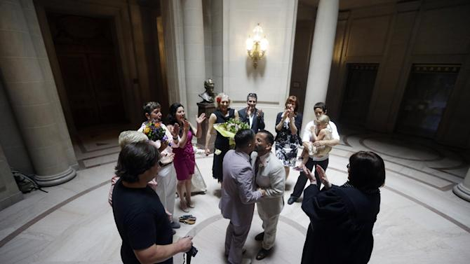 Peter Madril, center right, kisses Monte Young after the two were married at City Hall in San Francisco, Saturday, June 29, 2013. Dozens of gay couples waited excitedly Saturday outside of San Francisco's City Hall as clerks resumed issuing same-sex marriage licenses, one day after a federal appeals court cleared the way for the state of California to immediately lift a 4 ½ year freeze. Big crowds were expected from across the state as long lines had already stretched down the lobby shortly after 9 a.m. City officials decided to hold weekend hours and let couples tie the knot as San Francisco is also celebrating its annual Pride weekend expected to draw as many as 1 million people. (AP Photo/Marcio Jose Sanchez)