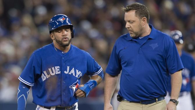 Toronto Blue Jays' Devon Travis, left, holds his left side while walking off the field with an apparent injury during first-inning baseball game action against the Atlanta Braves in Toronto on Sunday, April 19, 2015. (Darren Calabrese/The Canadian Press via AP) MANDATORY CREDIT