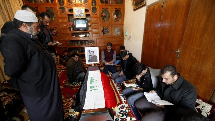 Relatives read from the Koran next to the coffin of Joumaili during his funeral in Falluja