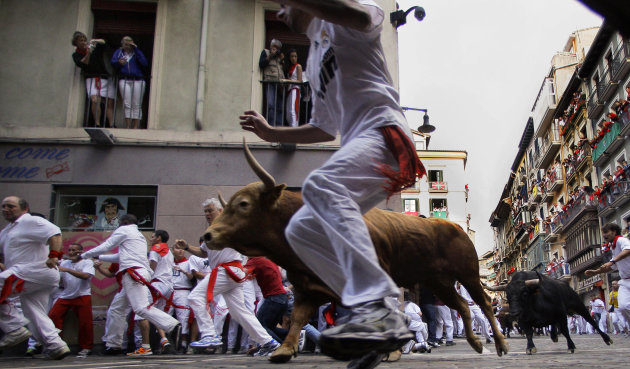 Revelers run on Estafeta corner with Torrehandilla's fighting bulls ranch, during the eighth and last running of the bulls at the San Fermin fiestas, in Pamplona northern Spain, Saturday, July 14, 201
