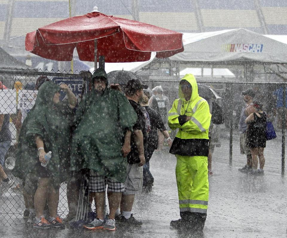 Fans try to stay out of the rain before the NASCAR Sprint Cup auto race at Kentucky Speedway in Sparta, Ky., Saturday, June 29, 2013. (AP Photo/Garry Jones)