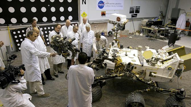 In this photo taken on Wednesday, Feb. 22, 2012,  National Aeronautics and Space Administration, NASA administrator, Charles Bolden, third from right, checks out a replica of the Mars Science Laboratory rover at NASA' Jet Propulsion Laboratory in Pasadena, Calif.  President Barack Obama's proposed budget calls for a 20 percent cut in NASA's planetary budget, forcing a restructuring of the Mars exploration program. Far left, Richard Cook, Deputy Project  Manager Mars Science Lab Mission. (AP Photo/Damian Dovarganes)