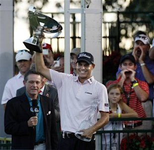 Bill Haas hoists the FedEx Cup from a stage overlooking the 18th green after winning the Tour Championship, the trophy for which is in his left hand,