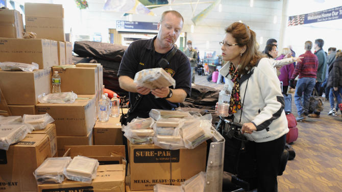 Bradley Airport firefighter Kelly Logan hands out a Meal Ready-To-Eat to Susan Pitkin while she waits for a flight at Bradley International Airport in Windsor Locks, Conn., Sunday, Oct. 30, 2011. (AP Photo/Jessica Hill)
