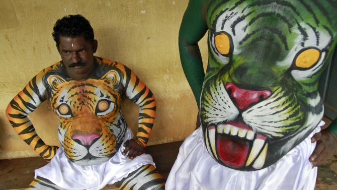 Dancers in body paint wait to take part in a performance during festivities marking the start of the annual harvest festival of Onam in Kochi