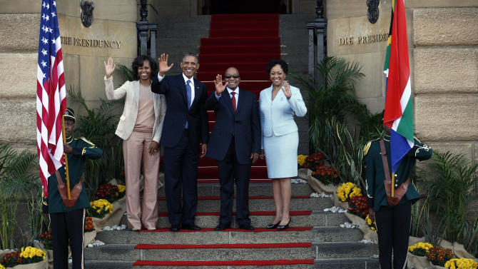 U.S. President Barack Obama, center left, flanked by First Lady Michelle Obama, left, waves with South African President Jacob Zuma and his wife Tobeka Madiba-Zuma on the steps of Union Building in Pretoria, South Africa, Saturday, June 29, 2013.(AP Photo/Jerome Delay)