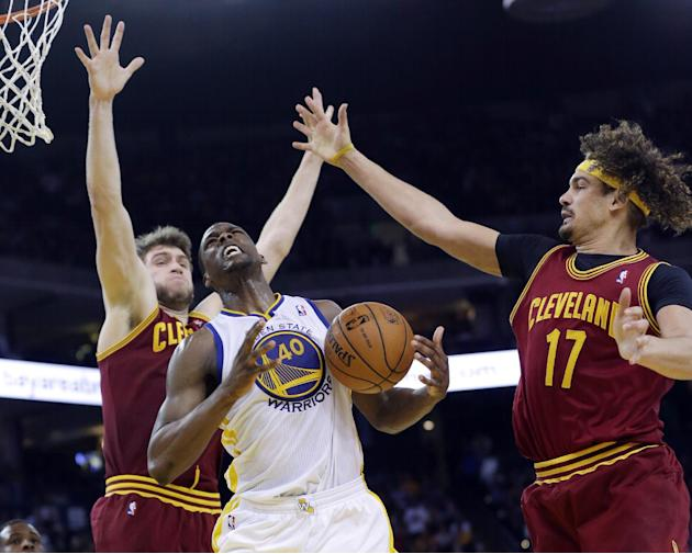 Golden State Warriors forward Harrison Barnes, center, goes up for a shot as Cleveland Cavaliers' Spencer Hawes, left, and Anderson Varejao (17) defend during the second half of an NBA basketball