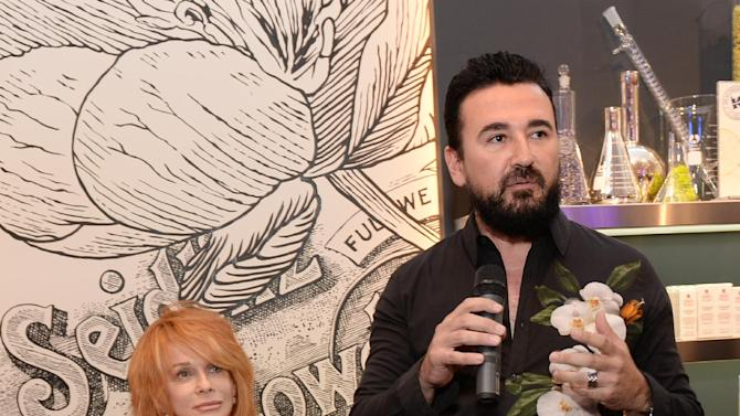 """Actress Ann-Margret sits on her pink Harley Davidson motorcyle with Kiehl's CEO Chris Salgardo at the Kiehl's Nolita Store during the """"Third Thursday"""" with Ann-Margret event on Thursday, Sept. 18, 2014, in New York. (Photo by Evan Agostini/Invision for Kiehl's/AP Images)"""