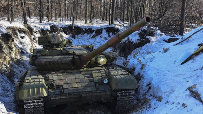 In this Wednesday, Jan. 14, 2015 photo Russian-backed separatist's tank is placed in a fortified position at the check-point north of Luhansk, Eastern Ukraine.  An attack on a passenger bus in eastern Ukraine killed 12 people Tuesday, likely dealing the final blow to hopes that a short-lived and shaky cease-fire could take hold. (AP Photo/ Mstyslav Chernov)