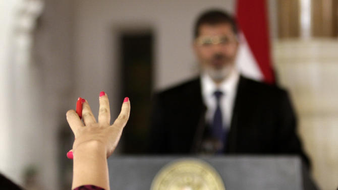 In this Friday, July 13, 2012 photo, a reporter, foreground, raises her hand to ask a question to Egyptian President Mohammed Morsi during a joint news conference with Tunisian President Moncef Marzouki, unseen, at the Presidential palace in Cairo, Egypt. Egypt's Islamist president may look like he's running out of options as he faces an appeals court strike and massive opposition protests over decrees granting himself near absolute power. Will he back down now? Most likely not. Mohammed Morsi's next move may be to raise the stakes even higher. Signs are growing the constitutional panel at the heart of the showdown could vote on a draft this week despite a walkout by liberal and Christian members. (AP Photo/Maya Alleruzzo)