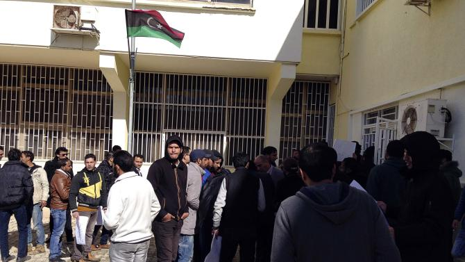 Demonstrators stand outside the headquarters of Libyan P< Thinni, as they demand the dismantling of his internationally recognised government, in Bayda