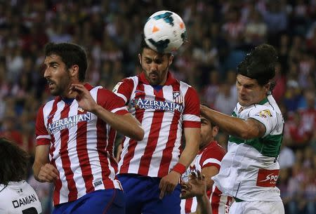 Atletico Madrid's Villa heads the ball next his teammate Garcia and Elche's Sapunaru during their Spanish first division soccer match at Vicente Calderon stadium in Madrid