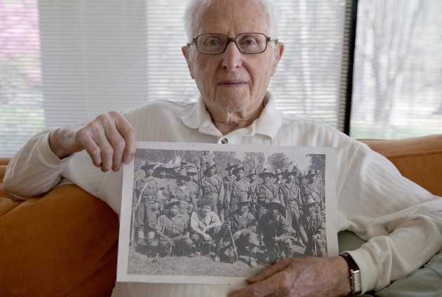 In this Monday, March 19, 2012 photo, World War II veteran Sam Spector holds a 1944 photo of himself, front row second from left, with Kachin Rangers, taken in northern Myanmar, at his home in Rome, G