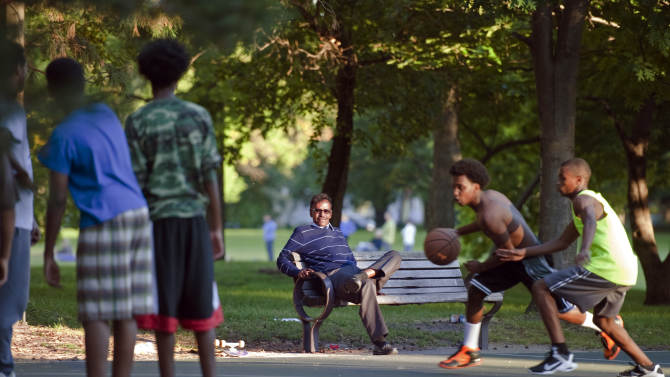 In this Monday, Sept. 22, 2014 photo, Abdirizak Bihi, right, executive director of the Somali Education and Social Advocacy Center, watches kids play basketball at Currie Park in Minneapolis, near a large Somali community in the Cedar Riverside neighborhood. While Bihi strolls through the neighborhood parks, he is on the lookout for anyone who might be trying to recruit the city's young Somalis to join jihad in Syria. (AP Photo/Craig Lassig)