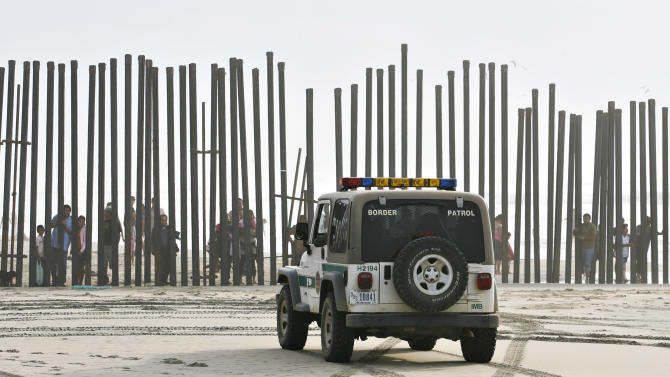 FILE -  In this Jan. 18, 2009 file photo, a U.S. Border Patrol vehicle sits parked in front of a crowd of people peering through the U.S.-Mexico border fence at Border Field State Park in San Diego. At one time, before the enhanced border fence in the area, the San Diego area held the most popular routes for illegal immigrants heading into the U.S. (AP Photo/Denis Poroy)