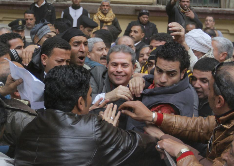 Tawfiq Okasha, center, a popular Egyptian TV presenter, is greeted by his supporters as he leaves the Cairo South court in Cairo Egypt, Tuesday, Jan. 8, 2013. An Egyptian court acquitted Okasha on charges of inciting the killing of the country's new president Mohammed Morsi. (AP Photo/Amr Nabil)