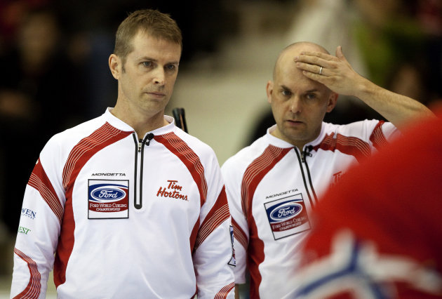 Canada's Skip Jeff Stoughton (L) talks with his third Jon Mead during their match against Norway in the evening draw at the Ford World Men's Curling Championships at the Brandt Centre in Regina, Saska