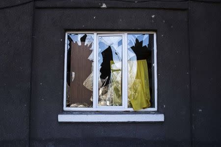 The broken window of a house damaged by fighting is seen in the town of Vuhlehirsk