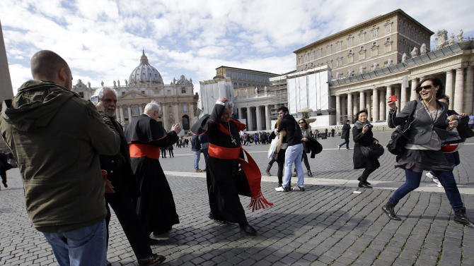Canadian Cardinals, Marc Ouellet, left and Thomas Christopher Collins are followed by tourists as they walk in St. Peter's Square at the Vatican, Saturday, March 9, 2013. The preliminaries over, Catholic cardinals are ready to get down to the real business of choosing a pope. And even without a front-runner, there are indications they will go into the conclave Tuesday with a good idea of their top picks. The conclave date was set Friday during a vote by the College of Cardinals, who have been meeting all week to discuss the church's problems and priorities, and the qualities the successor to Pope Benedict XVI must possess. (AP Photo/Gregorio Borgia)