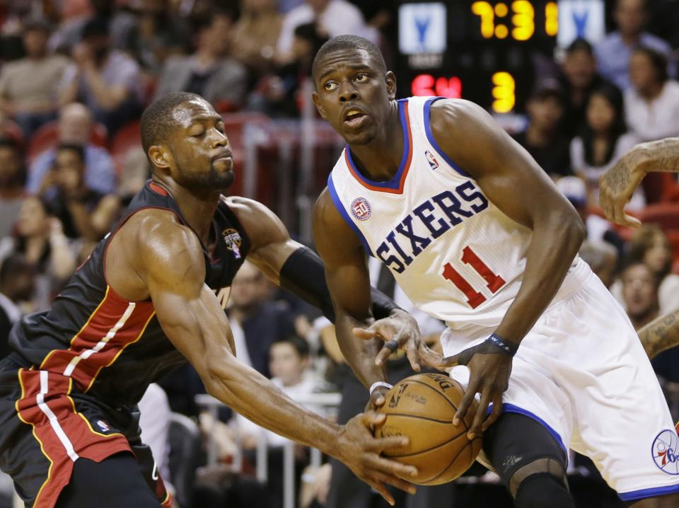 Miami Heat's Dwyane Wade (3) tries to steal the ball from Philadelphia 76ers' Jrue Holiday (11)  during the second half of a NBA basketball game in Miami, Friday, March 8, 2013. The Heat won 103-92.  (AP Photo/J Pat Carter)