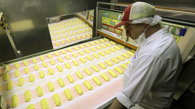 In this Wednesday, Feb. 13, 2013 photo, Roger Hildebeitel inspects Peeps as they move through the manufacturing process at the Just Born factory in Bethlehem, Pa. With the storied candy brand celebrating its 60th anniversary this year, a quirky new TV ad campaign talks about all the things people do with their Peeps. (AP Photo/Matt Rourke)