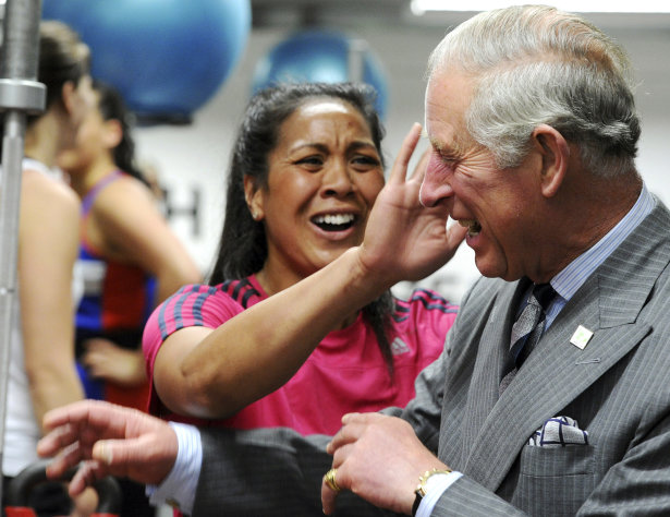 Britain&#39;s Prince Charles has sweat wiped from his face after receiving a hug from one of the members of the New Zealand women&#39;s sevens rugby team at the AUT Millennium, New Zealand&#39;s national training center for high performance sports, in Auckland, New Zealand, Monday, Nov. 12, 2012. (AP Photo/SNPA, Ross Setford)