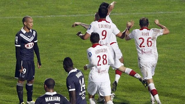 Lille's players celebrate after Marko Basa's goal against Bordeaux in the last minute at the Stade Chaban Delmas (Reuters)