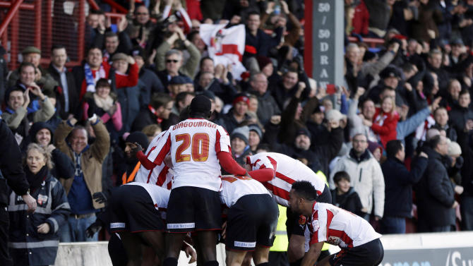 Brentford players celebrates after their teammate Marcello Trotta, obscured, scored against Chelsea during their English FA Cup fourth round soccer match in London, Sunday, Jan. 27, 2013. The match ended 2-2 draw. (AP Photo/Lefteris Pitarakis)