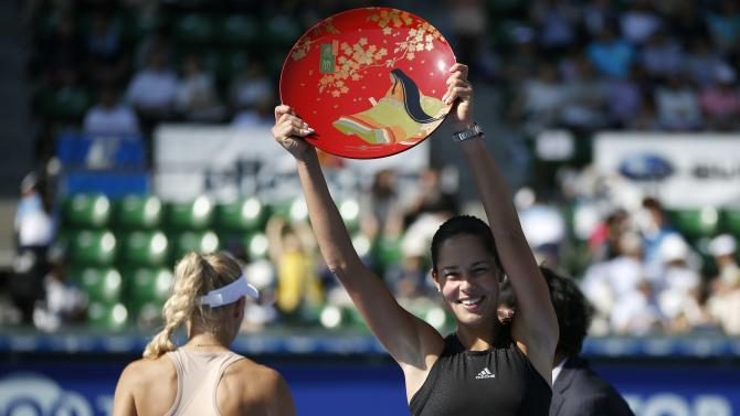 Ivanovic of Serbia holds up her trophy after defeating Wozniacki of Denmark during an award ceremony after their Pan Pacific Open women's singles final tennis match in Tokyo