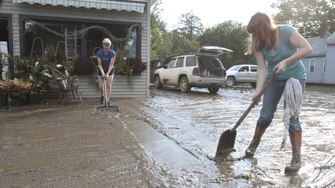 FILE-In this Aug. 29, 2011, file photo, Nina Brennan, right, and Phyllis Berry clean mud from in front of the Proud Flower store in the aftermath of Tropical Storm Irene in Waterbury, Vt.  Hard lessons have been learned in the year since Irene sent sedans bobbing down rivers, swept away historic covered bridges, put millions in the dark and killed more than 65 people all along the Eastern Seaboard. Responses range from personal gestures, like buying a home generator, to statewide policy changes, like the tightening of utility regulations. Many of the reactions are based on the belief that while Irene surprised areas more used to blizzards than tropical weather, future storms are inevitable. (AP Photo/Toby Talbot)