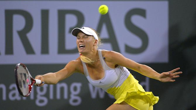 Caroline Wozniacki, of Denmark, returns a shot to Angelique Kerber, of Germany, at the BNP Paribas Open tennis tournament, Friday, March 15, 2013, in Indian Wells, Calif. (AP Photo/Mark J. Terrill)