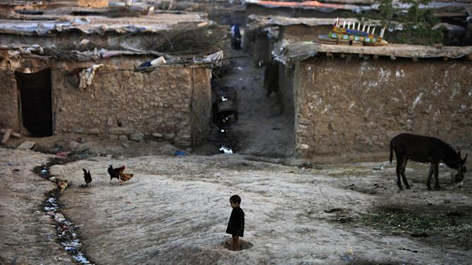 An Afghan refugee boy, center, watches chickens feeding in a neighborhood on the outskirts of Islamabad, Pakistan, Thursday, March 21, 2013. Pakistan hosts over 1.6 million registered Afghans, the largest and most protracted refugee population in the world, according to the U.N. refugee agency. (AP Photo/Muhammed Muheisen)
