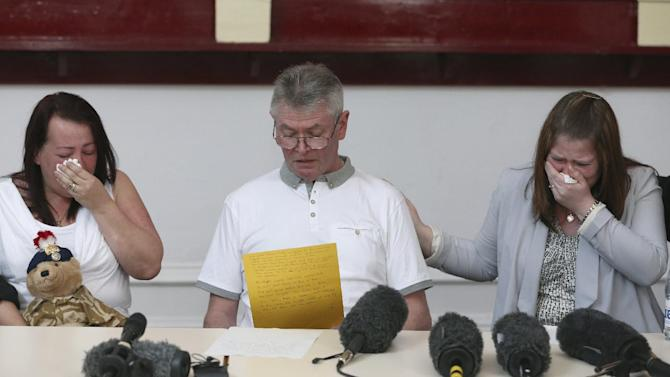 """Family members of murdered British soldier Lee Rigby, from left to right, his mother Lyn, stepfather Ian, and his wife Rebecca Rigby, as his stepfather reads a statement during a press conference at the Regimental HQ of his unit, the Royal Regiment of Fusiliers at Bury in Greater Manchester, England, Friday May 24, 2013. Ian Rigby thanked people for their support and including the tribute """"You fought bravely and with honour died"""".  Drummer Lee Rigby had served in Afghanistan and was attached to the Regimental Recruiting Team when he was hacked to death in broad daylight on Wednesday afternoon in Woolwich, south-east London. Two suspects were shot and arrested at the scene and remain in police custody. (AP Photo/Dave Thompson)"""