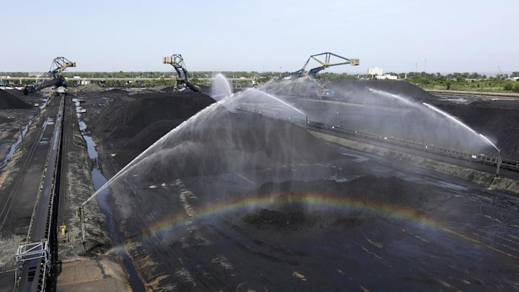 In this May 22, 2014 photo, a rainbow forms as sprinklers spray water to prevent coal dust from entering the air at Dominion Terminal Associates' coal terminal in Newport News, Va. As the Obama administration weans the U.S. off dirty fuels blamed for global warming, energy companies have been sending more of America's unwanted energy leftovers to other parts of the world. This fossil fuel trade threatens to undermine President Barack Obama's strategy for reducing the gases blamed for climate change and reveals a little-discussed side effect of countries acting alone on a global problem. (AP Photo/Patrick Semansky)