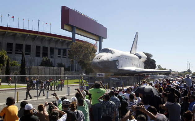 The space shuttle Endeavour moves north on Bill Robertson Lane in front of the Coliseum in Los Angeles Sunday, Oct. 14, 2012. In thousands of Earth orbits, the space shuttle Endeavour traveled 123 million miles. But the last few miles of its final journey are proving hard to get through. Endeavour&#39;s 12-mile crawl across Los Angeles to the California Science Museum hit repeated delays Saturday, leaving expectant crowds along city streets and at the destination slowly dwindling. Officials estimated the shuttle, originally expected to finish the trip early Saturday evening, would not arrive until later Sunday. (AP Photo/Alex Gallardo)