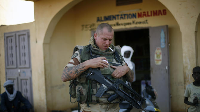 """A French soldier lights up a cigarette outside a food store in Gao, northern Mali, Tuesday Jan. 29, 2013, days after Malian and French military forces closed in and retook the town from Islamist rebels. Earlier Tuesday, four suspected extremists were arrested after being found by a youth militia calling themselves the """"Gao Patrolmen"""". Malian soldiers prevented the mob from lynching them. (AP Photo/Jerome Delay)"""