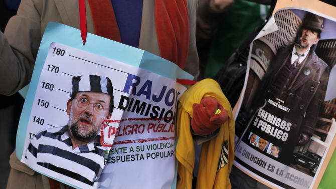 Protestors shout slogans 'there is money, the Popular Party's former treasurer have it' as they carry a banner reading, 'Spain's Prime Minister, Mariano Rajoy, resign! Public enemy, against your violence popular action' during a protest against a measure raising Court fees in Madrid, Saturday, Jan. 19, 2013. A former Spanish ruling party treasurer amassed 22 million euro ($29 million) in Swiss bank accounts, a court said, prompting a barrage of questions Friday about whether senior officials may have been involved in alleged corruption before taking power in 2011. (AP Photo/Andres Kudacki)