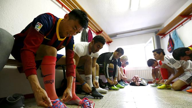 Members of ESV Neuaubing Sports United put on shoes before training session at football field in Munich